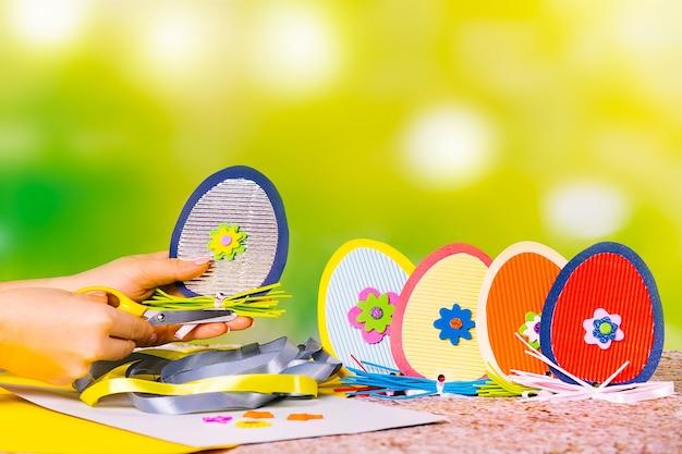 Dekorative handgefertigte eier aus handgefertigtem farbigem karton. material und hände mit einer leuchtenden schere auf einem grün.
