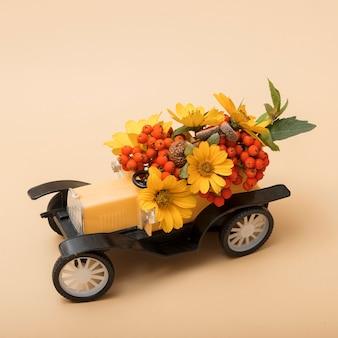 Dekorative herbstzusammensetzung eines spielzeugautos mit eberesche, blumen und blättern, eicheln