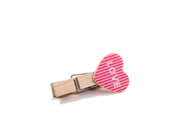 Dekorative hölzerne wäscheklammern mit roten herzen auf weiß. konzept der liebe und valentinstag.