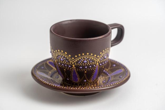 Dekorative keramik bemalte tasse und untertasse auf weißem hintergrund, nahaufnahme. dekorative porzellantasse und untertasse mit acrylfarben bemalt, handarbeit, punktmalerei