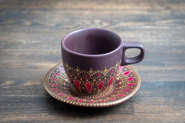 Dekorative keramik gemalte tasse und untertasse auf hölzernem hintergrund, nahaufnahme. dekorative porzellantasse und untertasse mit acrylfarben bemalt, handarbeit, punktmalerei