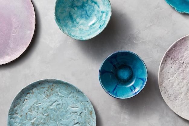 Dekorative keramik - schalen, teller mit glasur auf einer grauen wand bedeckt. draufsicht des traditionellen handgefertigten.