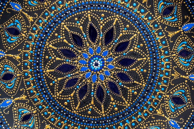 Dekorative keramikplatte mit schwarzen, blauen und goldenen farben, bemalte platte im hintergrund, nahaufnahme, draufsicht. detail porzellanteller mit acrylfarben bemalt, handarbeit, punktmalerei