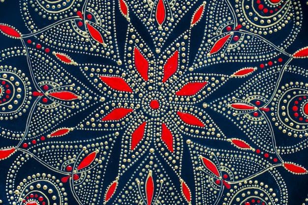 Dekorative keramikplatte mit schwarzen, roten und goldenen farben, bemalte platte im hintergrund, ansicht von oben. detail des porzellantellers mit acrylfarben bemalt, handarbeit, punktmalerei