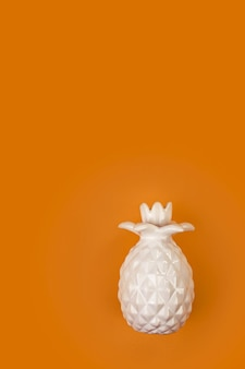 Dekorative keramische weiße ananas auf einer leuchtend orange oberfläche