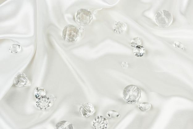Dekorative klare diamanten auf weißem strukturiertem stoffhintergrund