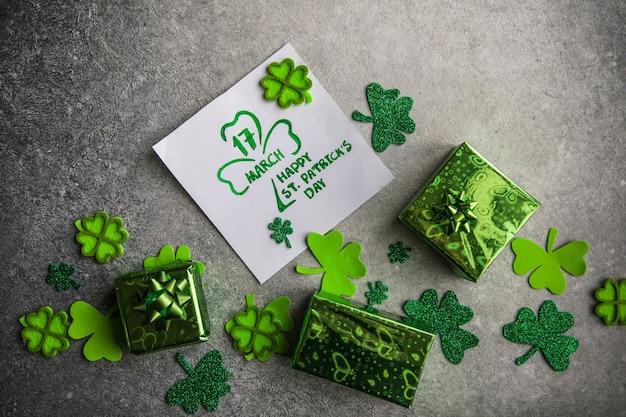 Dekorative kleeblätter, grüne geschenkbox, münzen auf steinhintergrund, flache lage. feier zum st. patrick's day. karte happy st. patrick's day