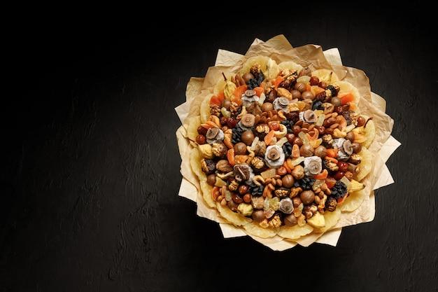 Dekorative komposition in form eines bouquets aus getrockneten früchten und nüssen