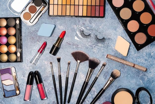 Dekorative kosmetik, make-up bürstet falsche wimpern auf blau