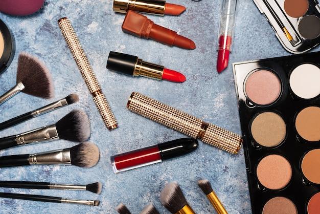 Dekorative kosmetik, make-up bürstet falsche wimpern auf blauem grund. der blick von oben