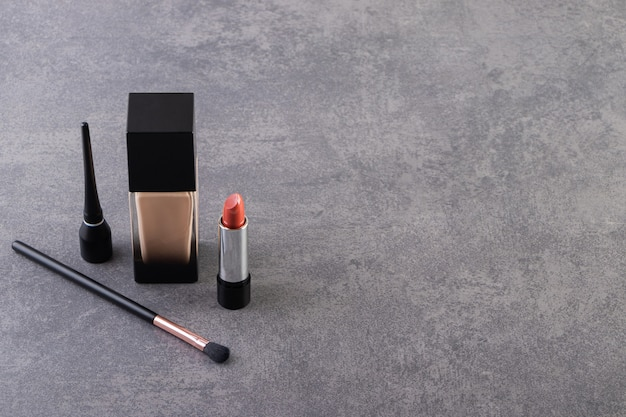 Dekorative kosmetik und make-up pinsel auf einem steintisch platziert.