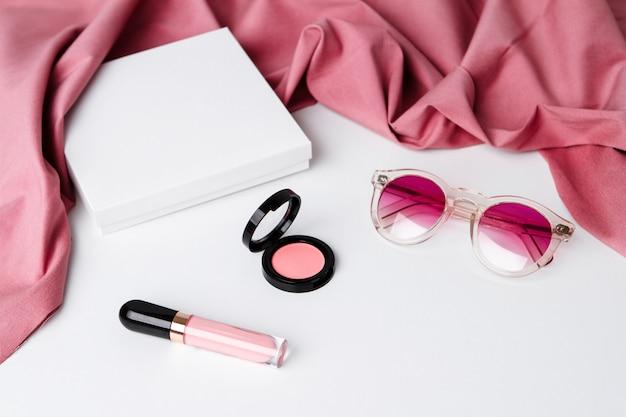 Dekorative kosmetik und sonnenbrille über weißer oberfläche
