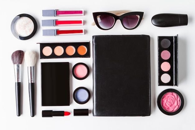 Dekorative kosmetiksonnenbrille und notizbuch über weißem hintergrund