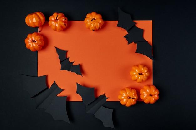 Dekorative kürbisse und papierfledermäuse auf schwarzem und orange hintergrund. halloween-feiertagskonzept. flaches layout, flatley