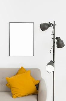 Dekorative lampe mit leerem rahmen und sofa