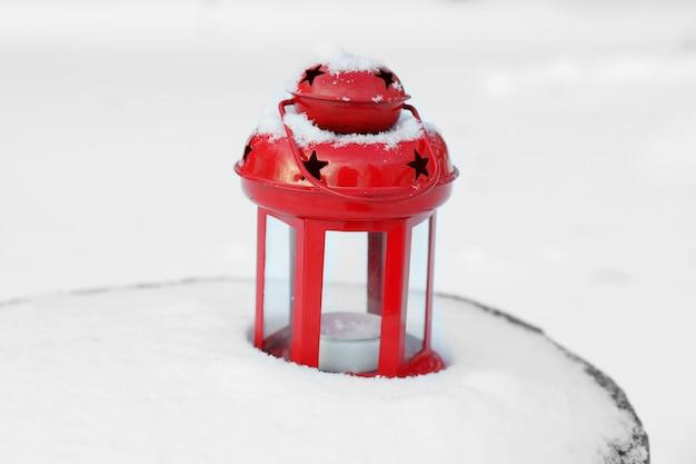 Dekorative laterne auf holzstumpf über schneeoberfläche