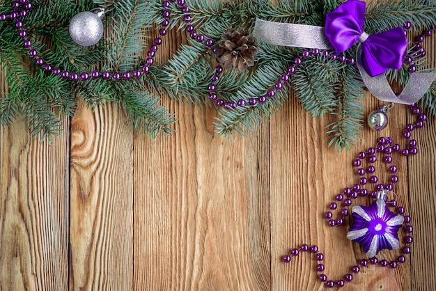 Dekorative lila schleife und band. weihnachtskomposition mit tannenzweigen. zapfen, perlen und kugeln auf holzbrett mit kopierraum.