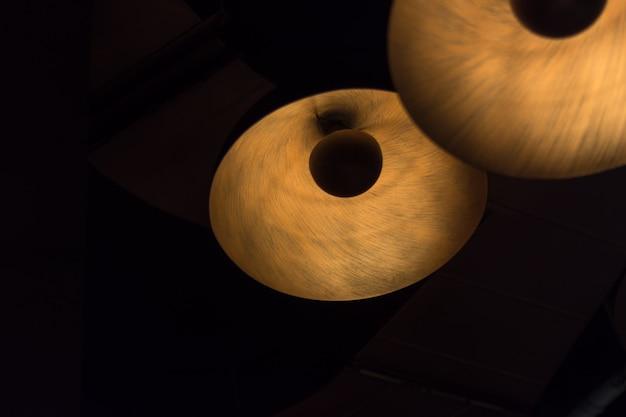 Dekorative moderne hölzerne laterne, die an der decke mit dunklem hintergrund hängt.