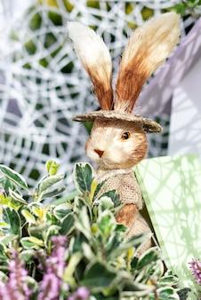 Dekorative osterkomposition mit niedlichem kaninchen und grünen pflanzen