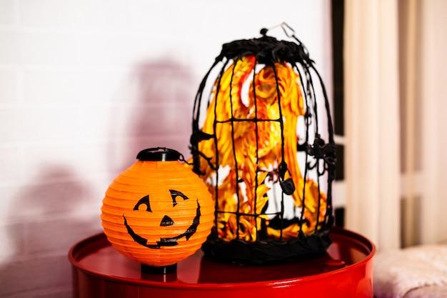 Dekorative papierkürbislaterne und -käfig mit orange spielzeugvogel. dekor für die feier von halloween