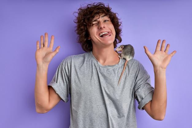 Dekorative ratte auf den schultern des fröhlichen mannes, hübscher kaukasischer junger mann hat keine angst vor exotischen tieren, haustieren. ratte kriecht auf t-shirt. lila hintergrund