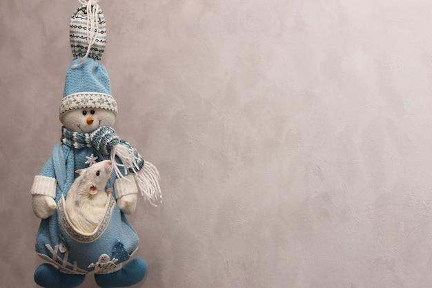 Dekorative ratte sitzt in der tasche gestrickter schneemann.
