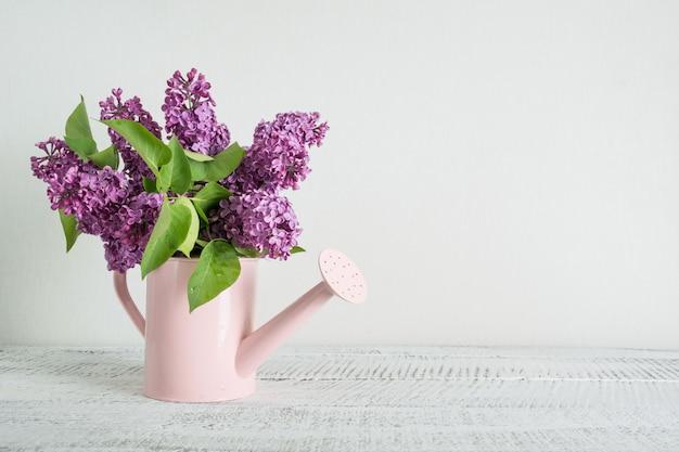 Dekorative rosa gießkanne mit purpurroten lila blumen auf weißem holztisch. gartenarbeitkonzept. frühling und sommer.