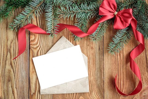 Dekorative rote schleife, band und umschlag mit weißer kartennotiz für text. weihnachtskomposition mit tannenzweigen, zapfen und kugeln auf holzbrett. speicherplatz kopieren.