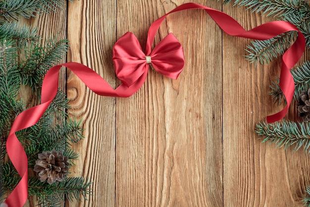 Dekorative rote schleife mit band und tannenzweigen auf hölzernem hintergrund. weihnachtskomposition mit kopierraum
