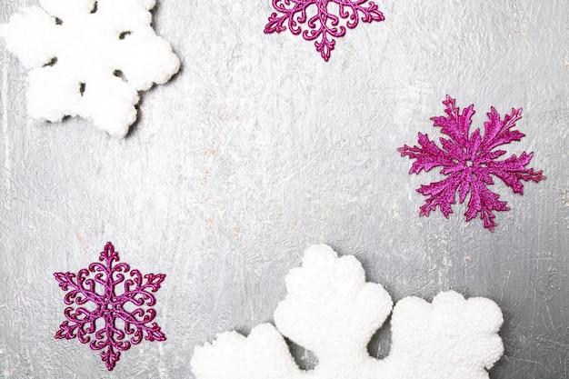 Dekorative schneeflocke weiß und rosa auf grauem hintergrund