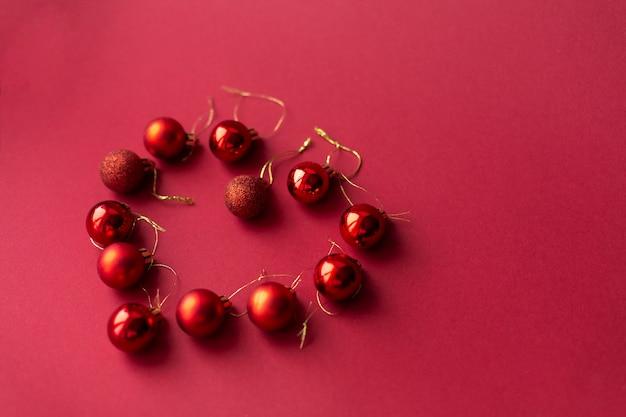 Dekorative spielzeugbälle des roten weihnachtsbaums auf dem roten feierlichen weihnachtshintergrund ausgebreitet in form eines herzens. neujahrsfeiertage. weihnachtsferien