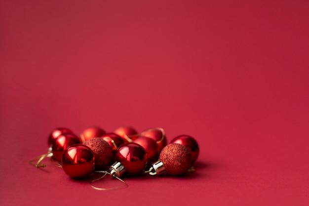 Dekorative spielzeugbälle des roten weihnachtsbaums auf rotem feierlichem weihnachten
