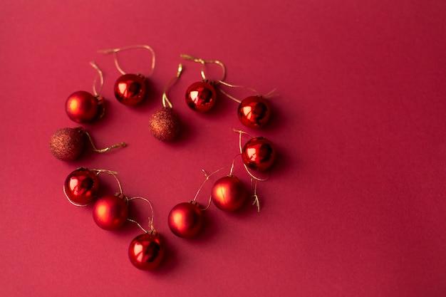 Dekorative spielzeugbälle des roten weihnachtsbaums auf rotem feierlichem weihnachtshintergrund