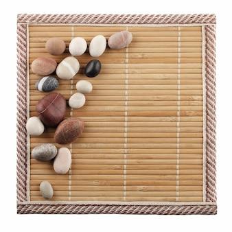 Dekorative steine sind auf der oberfläche des bambusteppichs
