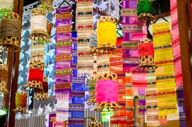 Dekorative weidenlaterne der nahaufnahme und lange flaggen lanna-gewebes (tung) hängen an der hotellobbydecke und am undeutlichen hintergrund.