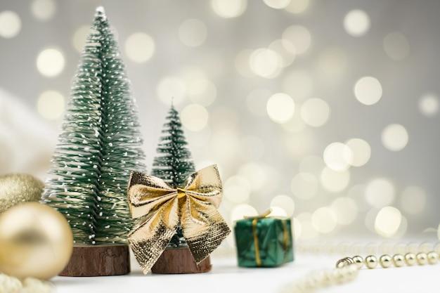 Dekorative weihnachtsbäume geschmückt und geschenke für das neue jahr auf dem hintergrund der goldenen bokeh-lichter, neujahrshintergrund,