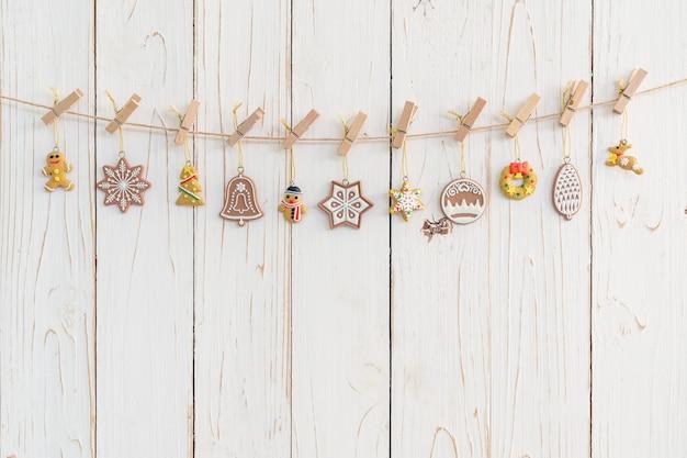 Dekorative weihnachtsdekoration, die an hölzernem für weihnachtshintergrund hängt