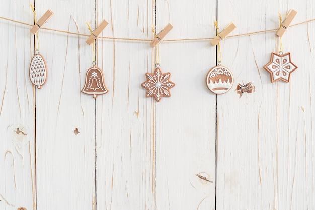 Dekorative weihnachtsdekoration, die an hölzernem für weihnachtshintergrund mit raum hängt