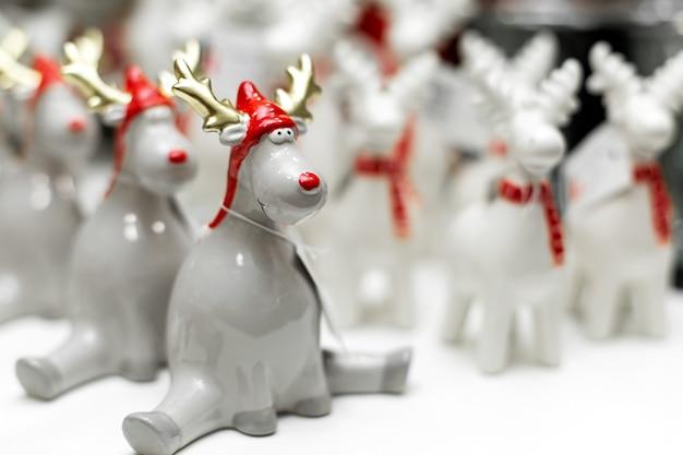 Dekorative weihnachtsfiguren. eine reihe von statuen von seltsamen weihnachtsrotwild sitzt in einer schnur. weihnachtsbaumschmuck. festliche einrichtung