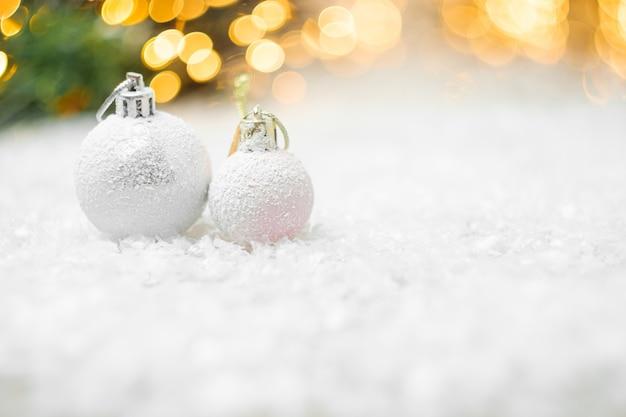 Dekorative weihnachtskugeln, die in einem schnee mit gelbem lichtbokeh liegen
