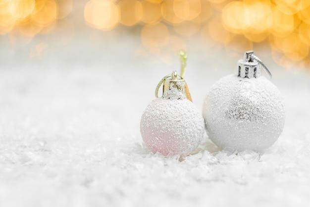 Dekorative weihnachtskugeln, die in einem schnee mit gelben bokeh-lichtern liegen
