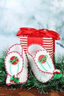 Dekorative weihnachtsschuhe mit geschenk auf dem tisch