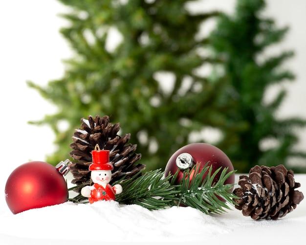 Dekorative weihnachtsverzierungen auf einer schneebedeckten oberfläche