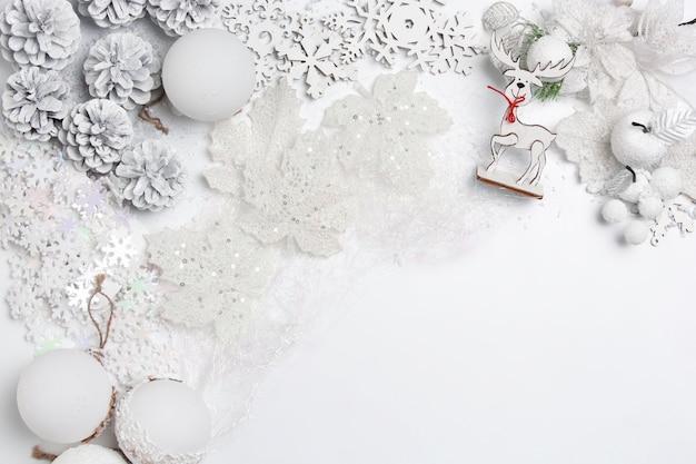 Dekorative weihnachtszusammensetzung von spielzeugen auf einem weißen tischhintergrund. draufsicht. flache lage