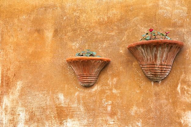 Dekorative weinlesewand mit steintöpfen