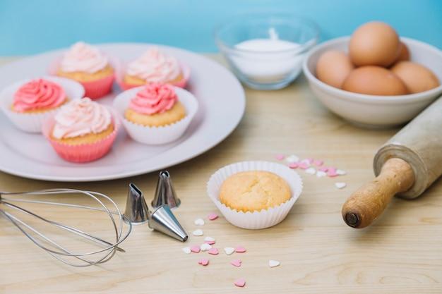 Dekorativer cupcake mit zutaten; schneebesen; streuen; nudelholz und düsen auf hölzernen schreibtisch