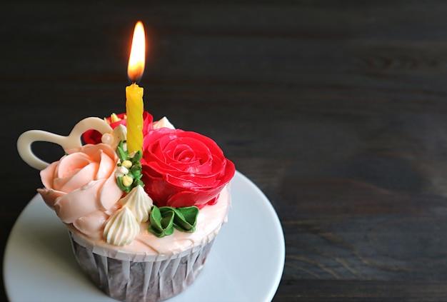 Dekorativer geburtstags-cupcake verziert mit rosenstrauß-förmigem zuckerguss mit einer leuchtenden kerze