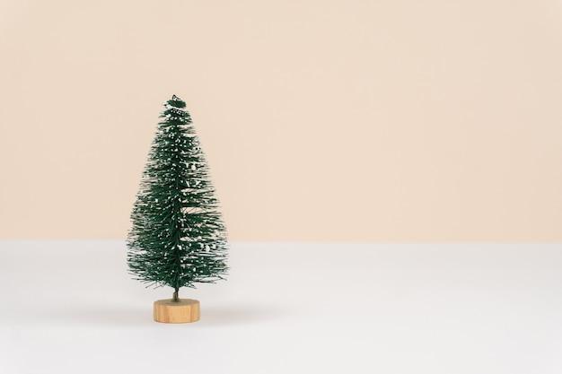 Dekorativer grüner weihnachtsbaum auf weißem tisch und pastellfarbener pfirsichwand