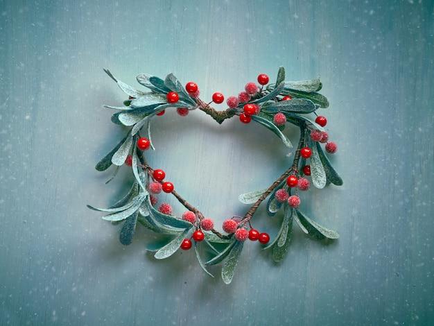 Dekorativer herzförmiger weihnachtskranz mit gefrosteten mistelblättern und roten beeren, die an einer hellen strukturierten holztür hängen