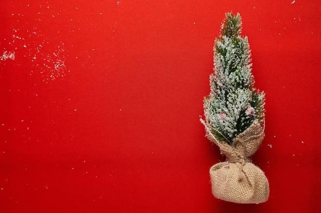 Dekorativer kleiner weihnachtsbaum auf rotem grund